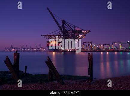 Ein Containerschiff im Hafen im Hafen von Felixstowe Wird geladen bei Nacht mit den alten Pier in den Vordergrund/Entladen - Stockfoto