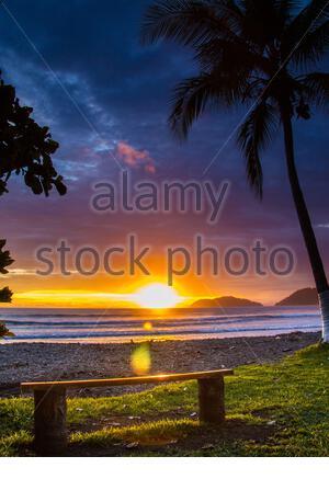 Gegen die im Pazifischen Ozean die Sonne für ein Bad geht, diese Bank ist ein perfekter Ort der Ruhe eines Costa Rica Sonnenuntergang zu genießen. - Stockfoto