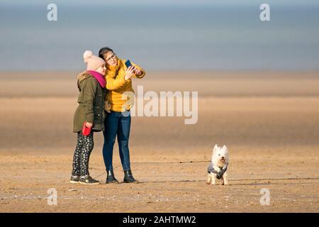 Southport, Merseyside, 1. Januar 2020. Zeit für eine selfie wie zwei Mädchen, die ihren Hund in der neuen Jahre Tag Sonnenschein Spaziergang entlang den Ufern von Southport Strand in Merseyside. Credit: cernan Elias/Alamy leben Nachrichten - Stockfoto