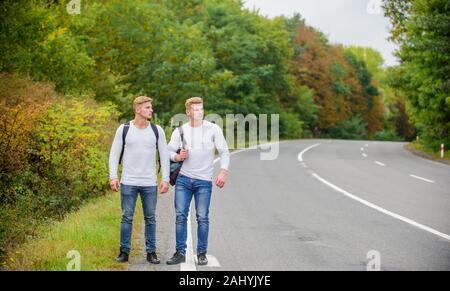 Gehen müssen. wanderlust Konzept. Wandern mit Freunden ist cool. gegangen, sich selbst zu finden. Reise trampen. Zwillinge zu Fuß entlang der Straße. Trampen auf leere Straße. Anreise per Trampen. Road Trip. - Stockfoto