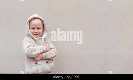 Kleinen Jungen 3-5 Jahre, glücklich, Lächeln, freut sich und lacht, Hintergrund beige Wand. Warmer Pullover mit Kapuze. Gefühle der Freude, Spaß und Entspannung - Stockfoto