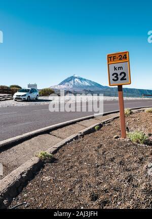 Km 32 der TF-24 Schild in den Nationalpark Teide auf Teneriffa mit einem geparkten Auto und den Berg Teide im Hintergrund. - Stockfoto