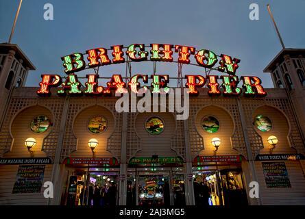 Das farbenfrohe, beleuchtete Schild des Brighton Palace Pier leuchtet in der Abenddämmerung. Der berühmte Pier in Brighton ist eines der beliebtesten Reiseziele in Großbritannien. - Stockfoto