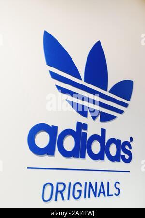 Adidas Originals Schriftzug auf der weißen Wand - Stockfoto