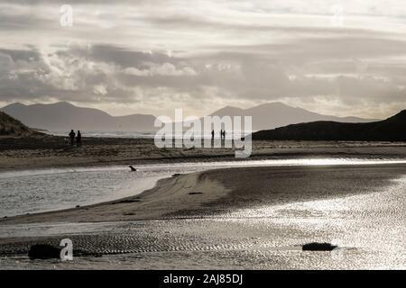 Hintergrundbeleuchtung Blick über Afon Ffraw Fluss mit Menschen zu Fuß auf Traeth Mawr Strand mit Berge im Winter. Aberffraw ISLE OF ANGLESEY Wales UK - Stockfoto