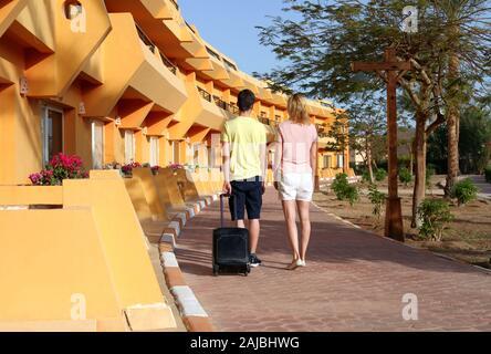 Junges Paar stehen im Hotel bei der Ankunft, auf der Suche nach Zimmer, Koffer Holding - Stockfoto