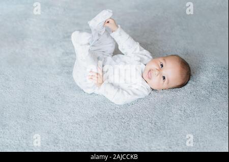 Baby Boy liegen und entspannen auf Bett Weiß im Schlafzimmer und seine Beine Holding. Nahaufnahme der Beine. Neugeborene 4 Monat Fähigkeiten Konzept. - Stockfoto