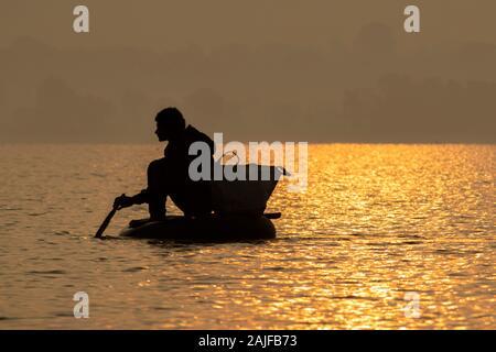 Bichhiya/Indien/November 29, 2019 - Silhouette Foto indische Fischer fischen im Teich durch das Sitzen in einem Schlauch. - Stockfoto