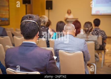 Nicht erkennbare Mann mit Kopfhörern für die Übersetzung während der Videokonferenz. kahle Wachmann mit dem Headset Volk zu kontrollieren. hitzige Debatte - Stockfoto