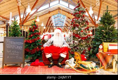 TALLINN, Estland - 22 Dezember, 2019: Santa Claus sitzt zwischen dekorierte Tannenbäume in Balti Jaam Markt bulding in Tallinn Estland im Dezember 2019 - Stockfoto