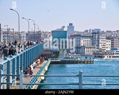 Galata Brücke und Bosporus. Viele Menschen wandern und Angeln auf der Brücke unter Tageslicht. Wohngebäude und Metall Geländer. - Stockfoto