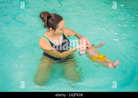 Schöne Mutter lehre Cute Baby Mädchen, wie sie in einem Pool schwimmen. Kind Spaß im Wasser mit Mom - Stockfoto