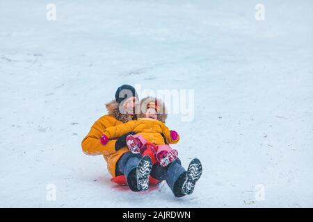 Vater mit Tochter in gelb Wintermäntel Schiebetüren verschneiten Hügel - Stockfoto