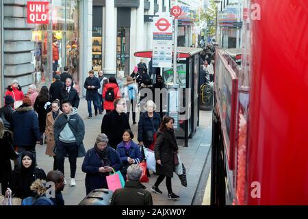Menschen Käufer tragen winter Bekleidung stehend Warten auf einen Bus an einer Bushaltestelle außerhalb Uniqlo Store in der Oxford Street London England UK KATHY DEWITT - Stockfoto