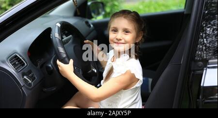 Gerne kleine Mädchen hinter dem Steuer des Papa's Auto sitzen - Stockfoto