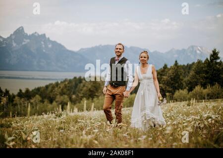 Braut und Bräutigam spazieren durch Wildblumen vor den Teton Bergen