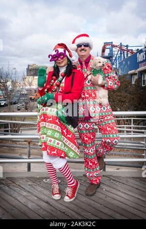 Stellen Portrait von ein paar & ihren Hund in hässlichen Weihnachten Outfits auf dem Boardwalk in Coney Island am Tag der Eisbär neue Jahre Tag schwimmen. - Stockfoto