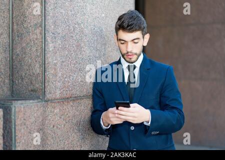 Hipster Geschäftsmann mit Bart und Anzug und Handy Outdoor im Sommer in der Stadt - Stockfoto