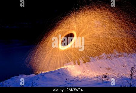 Brennende Stahlwolle Feuerwerk spinning neben einem See Stockfoto