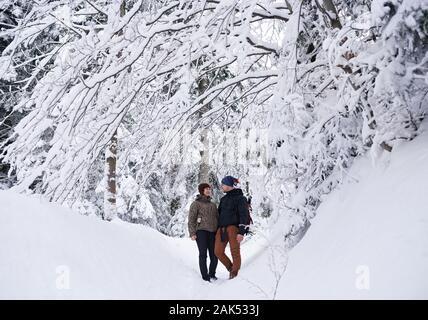 Lächelndes Paar in einem verschneiten Wald, Wandern - Stockfoto