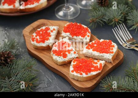 Sandwiches mit rotem Kaviar sind auf einem Holzbrett vor einem dunklen Hintergrund entfernt - Stockfoto