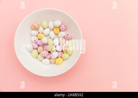 Frohe Ostern Konzept. Vorbereitung für den Urlaub. Ostern Süßigkeiten Schokolade Eier und fruchtgummi Bonbons auf trendigen Pastellfarben rosa Hintergrund isoliert. Einfache Minimalismus flach Ansicht von oben kopieren Raum - Stockfoto