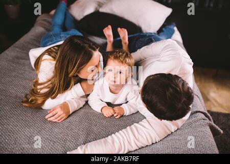 Happy Family ist Spaß haben im Schlafzimmer. Genießen, zusammen zu sein. Eltern sind Kitzeln ihren kleinen Sohn im Bett lag. Freundliche Familie spielen - Stockfoto