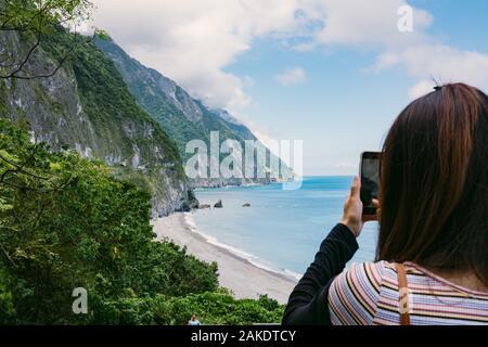 Ein Tourist verwendet ihr Telefon, um ein Foto von Qingshui Cliff zu machen, das von der Küstenstraße in der Nähe des Taroko National Park, Taiwan, gesehen wird - Stockfoto