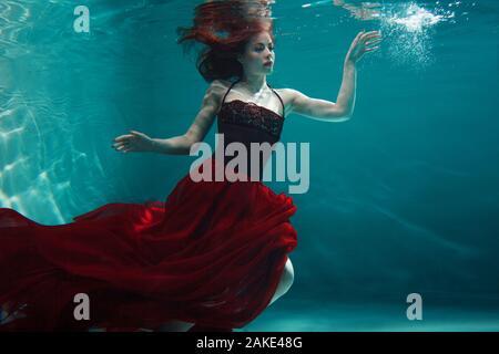 Schönes Mädchen in einem roten Kleid schwimmt unter Wasser. Wunderschönes Unterwasserfoto. Tauchen Sie unter Wasser, Surrealismus und Konzept. - Stockfoto