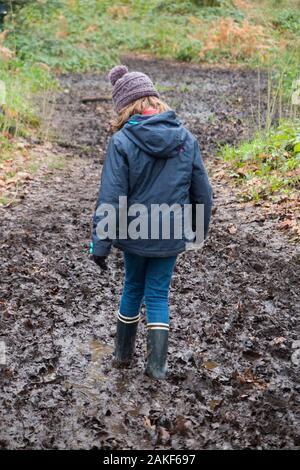 Junges Mädchen Alter 7, tragen Gummistiefel, genießt und Spielen in einem grossen nassen schlammigen Pfütze während einer Familie zu Fuß über Oxshott Gemeinsame, Esher, Surrey. Großbritannien (115) - Stockfoto
