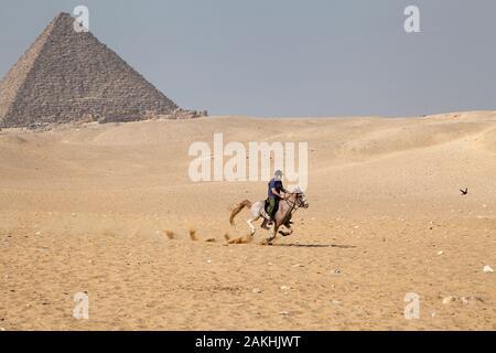Ein Mann reitet auf einem Pferd durch die Wüste Sand auf Gizeh Plateau in der Nähe der Pyramiden von Ägypten - Stockfoto