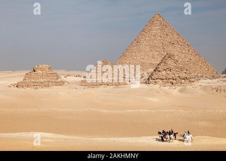 Menschen Reiten durch die Wüste Sand auf Gizeh Plateau in der Nähe der Pyramiden von Ägypten - Stockfoto