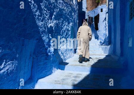 Einsamer Mann in Djellaba, der in Medina von Chefchaouen (auch Chaouen genannt), Marokko, spazieren geht - Stockfoto