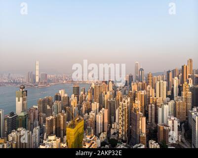 Luftaufnahme der Sonnenuntergang über den sehr überfüllten Wohngebieten von Kennedy Town und Sai Ying Pun auf Hong Kong Island und Kowloon im Hintergrund über - Stockfoto