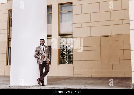 Afrikanisches männliches Modell in einem braunen Anzug, der außen posiert, Wandhintergrund mit Kopierraum, stilvoller Luxus teurer Business-Look, gut gekleideter Gentleman - Stockfoto