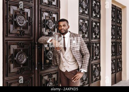 Afrikanisches männliches Modell in einem braunen Anzug, der sich nach draußen stellt, sich an die dekorierte Wand lehnt, Eingangstür, stilvoller Luxus teurer Business-Look, gut gekleidet - Stockfoto