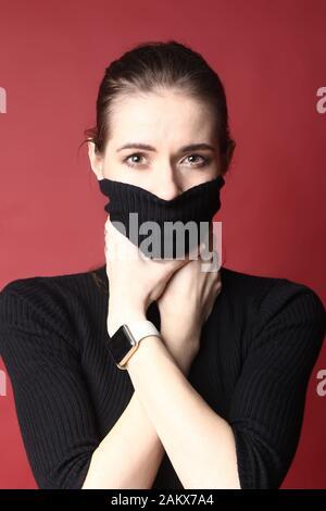 Junge Geschäftsfrau strangt sich auf rotem Hintergrund. - Stockfoto