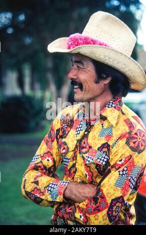 Trägt ein schickes Hemd und eine rosa Blume lei Um seinem Strohhut, eine hawaiische Paniolo (Cowboy) kleidet sich der jährlichen 4. Juli Rodeo am historischen Parker Ranch auf der grossen Insel von Hawaii in Hawaii, USA zu besuchen. Gebürtige Hawaiianer wurde Cowboys vor langer Zeit, im Jahre 1847, wenn die Rinder Ranch war auf dem Pazifischen Ozean Insel gegründet und wuchs zu einem der größten privaten Ranches in den Vereinigten Staaten zu werden. Heute ungefähr 17.000 Angus, Charolais Rind rinder weiden auf den Wiesen der Parker Ranch, die sich auf 130.000 Hektar (52,610 ha) in der Mitte der grossen Insel. - Stockfoto