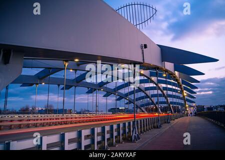 Suspension Bridge Kotlarski über der Weichsel in Krakau, Polen, gegen Licht der untergehenden Sonne. Vorbeifahrende Autos leichte Wanderwege, mit Blick auf Strasse. - Stockfoto