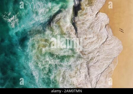 Luftaufnahmen von türkisblauen Meereswellen, die am Ufer des unberührten, abgeschiedenen Strandes in Bali, Indonesien, aufbrechen. - Stockfoto