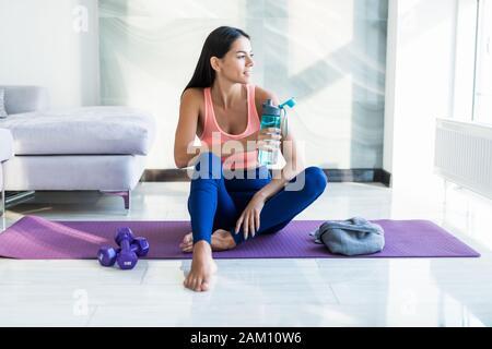 Durstgefühl. Müde Mädchen in Sportbekleidung Trinkwasser während der Sitzung auf die Gymnastikmatte