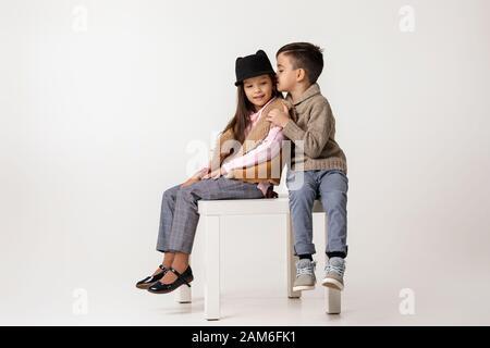 Niedlich stylisches Mädchen und Junge in modischen Kleidungsstücken sitzen im Studio zusammen. Kinderjunge umarmt Mädchen und erzählt ihr eine lustige Geschichte. Kinder fetzen - Stockfoto
