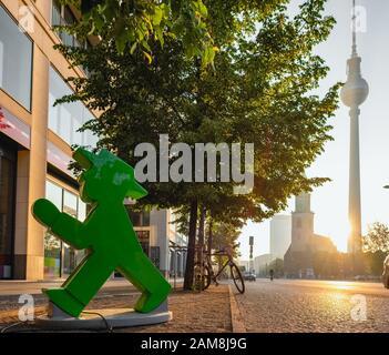 Statue einer ampelmann-figur mit Berliner fernsehturm bei Sonnenaufgang in Berlin im Hintergrund - Stockfoto