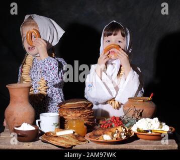 Zwei kleine Mädchen am Ferientisch. Maslenitsa - Stockfoto