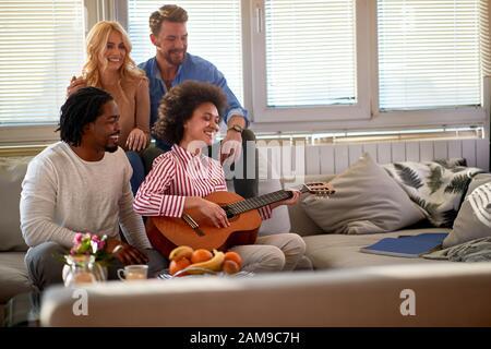 Junge Frau spielt Gitarrenende hängen mit Freunden aus Stockfoto