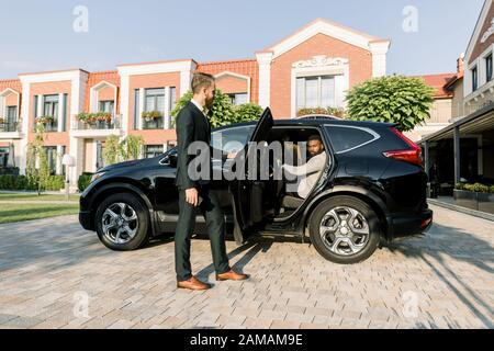 Der junge Mann, der auf dem Parkplatz auf seinen afrikanischen Mann wartet, hilft ihm, in den schwarzen Crossover zu kommen, draußen - Stockfoto