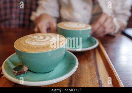 Zwei Tassen Cappuccino mit kleinem Herzen und lassen Muster aus Latte Kunst in blassgrünen Keramikbecher auf Holztablett und verwischen Hintergrund des gemütlichen Cafés. Stockfoto