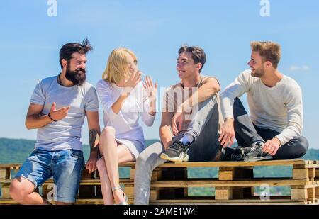 Vier Personen. Ideal für den Tag. Beste Freunde. Sommerurlaub: Verschiedene junge Leute reden zusammen. Eine Gruppe von Leuten in legerer Kleidung, glückliche Männer und Mädchen entspannen sich. Gute Idee. - Stockfoto