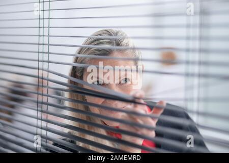 Lächelnde Geschäftsfrau, die durch die Jalousien des Bürofensters schaut - Stockfoto
