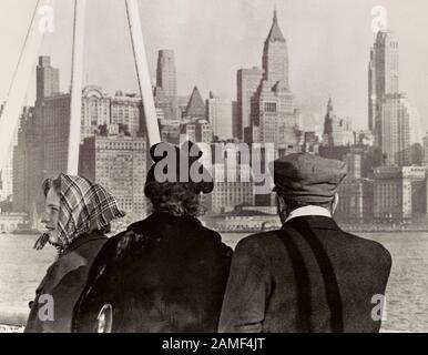 Eine Einwandererfamilie blickt auf die Skyline von New York, als sie von Deutschland aus an Bord der S. S. Nieuw Amsterdam in die USA kommen. Lower Manhattan, Neu - Stockfoto